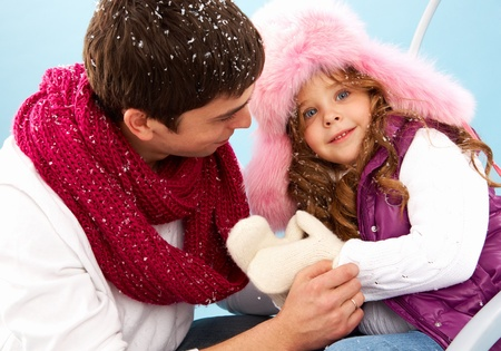 winterwear: Happy girl in furry hat and her father Stock Photo