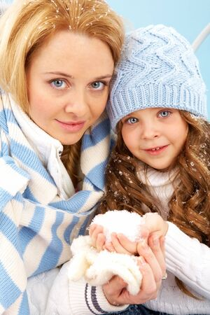 Portrait of mother and her daughter in winter clothes looking at camera Stock Photo - 11064399
