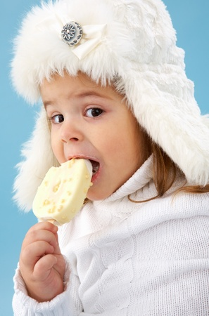Little girl in white furry hat eating ice-cream photo