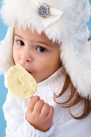 Little girl in white furry hat eating delicious ice-cream photo