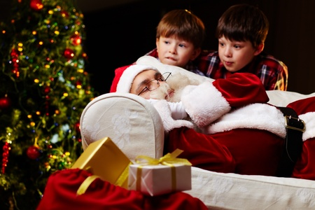 Photo of Santa Claus sleeping on sofa with two amazed kids near by photo