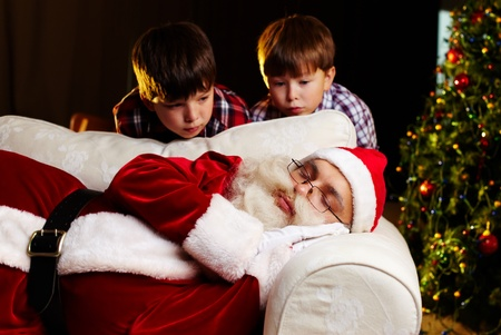 Photo of Santa Claus sleeping on sofa with two amazed kids looking at him photo