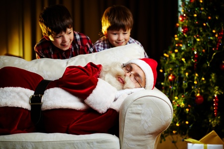 Photo of Santa Claus sleeping on sofa with two happy boys looking at him photo