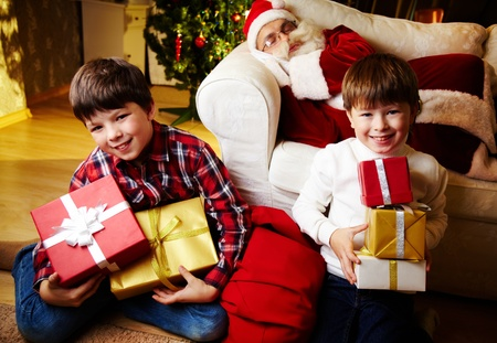 Photo of happy boys looking at camera with Santa Claus sleeping on sofa on background photo