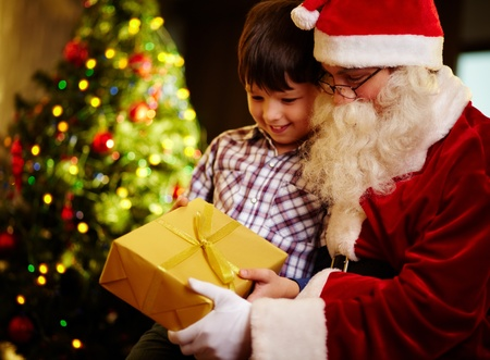 two boys: Photo of cute boy and Santa Claus holding giftbox and looking at it Stock Photo