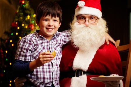 eating pastry: Photo of cute boy and Santa Claus looking at camera Stock Photo