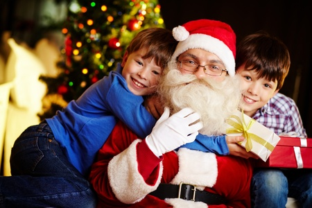 Photo of happy boy embracing Santa Claus with cute kid near by photo