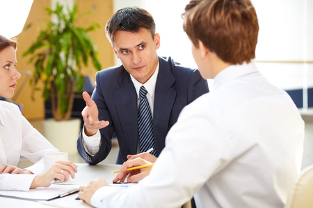explain: Serious boss giving some information to young office workers  Stock Photo