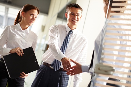 Business leader handshaking with his employee with secretary near by  photo