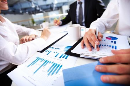 recursos financieros: Manos de gente de negocios sobre los documentos