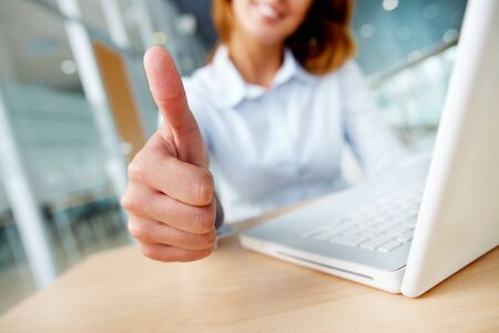 Image of businesswoman showing thumb up at workplace  photo