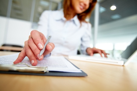 summary: Human hand with pen over paper during work in office