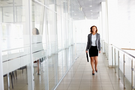 Businesswoman walking along the office corridor photo