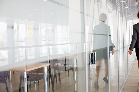 glass door: Reflection of businesswoman walking along the office corridor