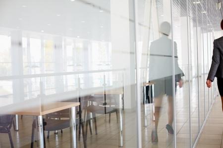 Reflexión de la empresaria caminando por el pasillo de oficina Foto de archivo