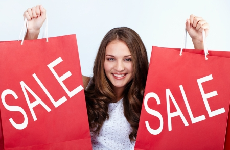 bargain: Happy girl holds red paperbags with symbol of sale and looking at camera Stock Photo