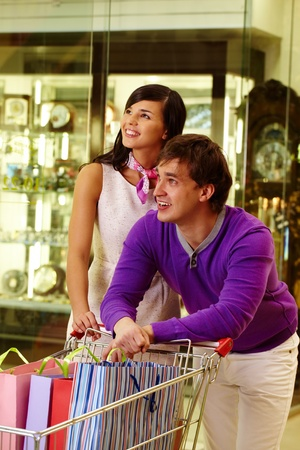 Portrait of happy couple looking at something during shopping in the mall photo