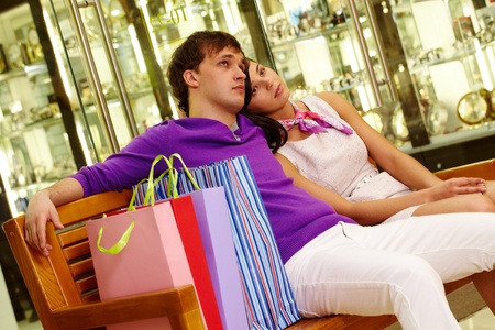 Two shopaholics having rest after good shopping in the mall photo