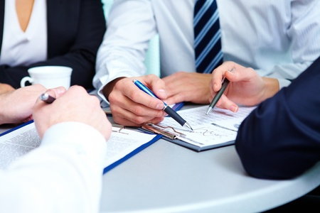 reviewing documents: Image of human hands during discussion of business plan at meeting Stock Photo