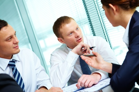 Image of confident colleagues listening to new ideas at meeting photo