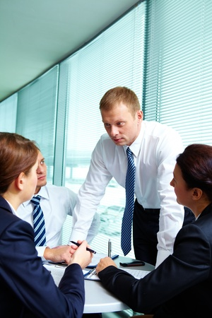serious woman: Image of smart employees looking at confident businessman while he explaining something in office Stock Photo