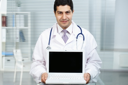 Portrait of happy doctor with open laptop looking at camera photo