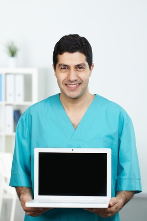Portrait of happy surgeon with open laptop looking at camera Stock Photo - 11223071