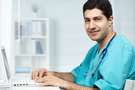 latino: Portrait of happy surgeon typing on laptop and looking at camera Stock Photo
