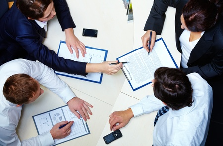 the signature: Above view of several business partners discussing contract