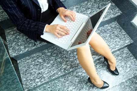 Close-up of businesswoman with laptop working on staircase photo