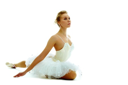 stretched: Portrait of graceful ballerina seated with stretched arm on white background Stock Photo
