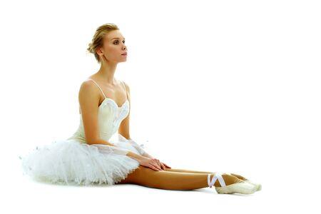 mujeres sentadas: Retrato de bailarina elegante sentado con las piernas estiradas en el fondo blanco