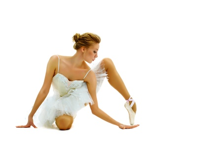 Portrait of graceful ballerina keeping balance on white background