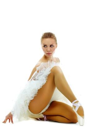 Portrait of graceful ballerina keeping balance on white background photo