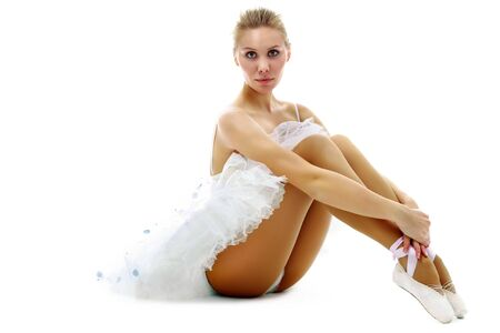 Portrait of graceful ballerina looking at camera on white background photo