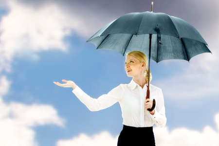 Happy businesswoman under open umbrella stretching her arm photo