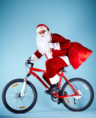 Photo of happy Santa Claus with red sack riding bike Stock Photo - 11223072