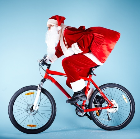 Photo of Santa Claus with red sack riding bike photo