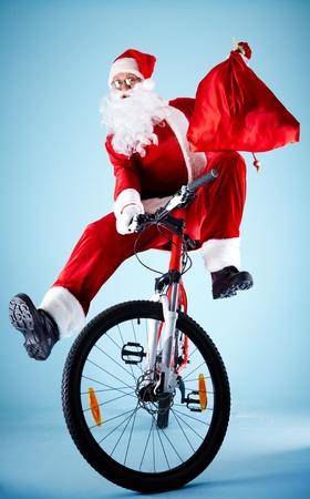 Photo of joyful Santa Claus with red sack on bike looking at camera photo