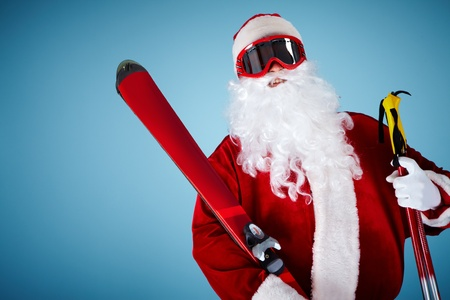Photo of happy Santa Claus with skis looking at camera photo