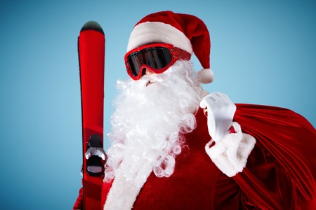 Photo of happy Santa Claus with skis and sack looking at camera photo