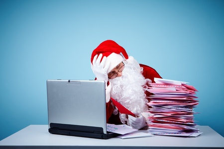 Portrait of Santa Claus touching head while looking at heap of letters in front of laptop photo