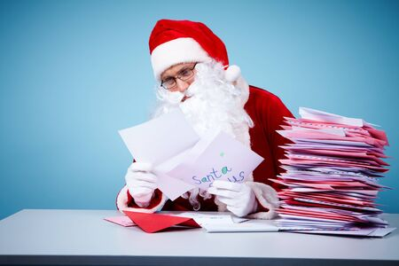 Portrait of Santa Claus reading letters with Christmas wishes photo