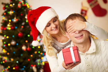 Portrait of happy woman closing male's eyes by her hands while holding giftbox in front of him