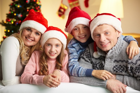 Portrait of four happy family members in Santa caps looking at camera with smiles Stock Photo - 11242412