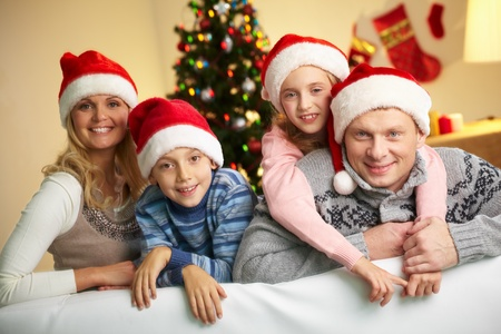 Portrait of four happy family members in Santa caps looking at camera with smiles Stock Photo - 11236310