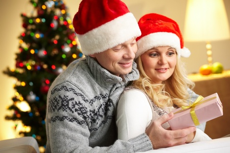 Portrait of surprised woman looking at giftbox in her husband hands while being embraced by him photo