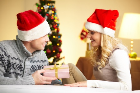 Portrait of surprised woman looking at giftbox in her husband hands on Christmas day Stock Photo - 11236368