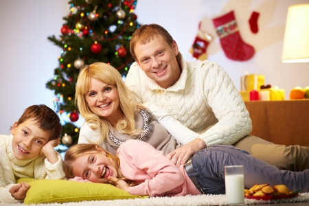 Portrait of four happy family members at home on Christmas Eve photo