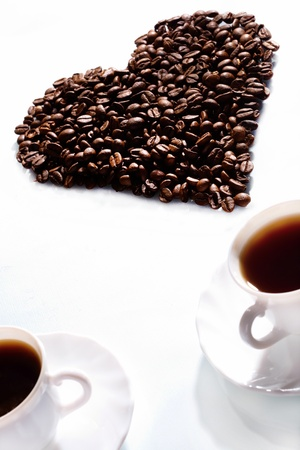 Image of coffee beans in shape of heart with two cups of espresso near by photo
